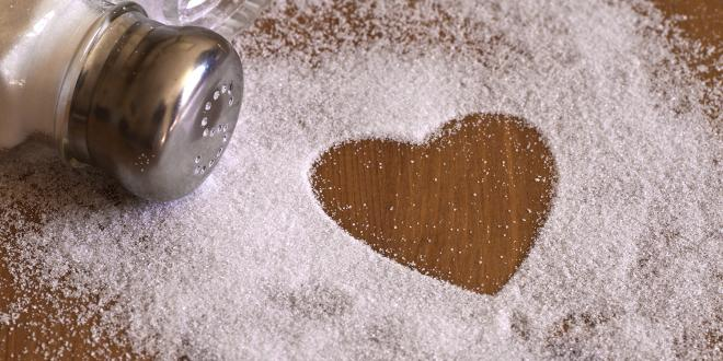 A salt shaker spilled out into a heart shape